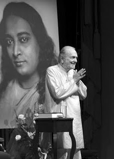 Swami Kriyananda on stage with a photo of Yogananda